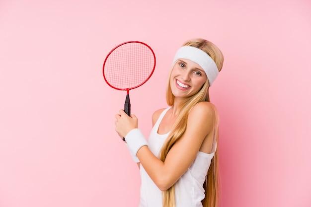 Joven mujer rubia jugando bádminton aislado