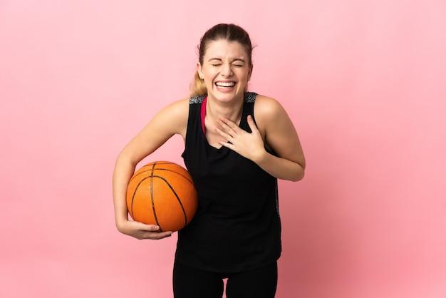 Joven mujer rubia jugando baloncesto sobre fondo rosa sonriendo mucho