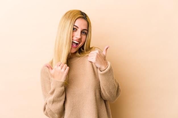 Joven mujer rubia levantando ambos pulgares, sonriente y confiada