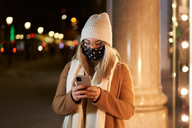Joven mujer rubia con una máscara delante de un escaparate escribiendo un mensaje, en una ciudad por la noche. ambiente invernal.