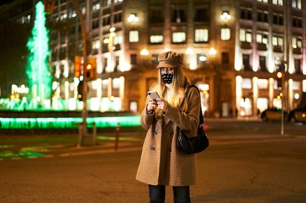 Joven mujer rubia con una máscara, usando un teléfono inteligente, escribiendo un mensaje de pie en una ciudad por la noche. ambiente invernal.