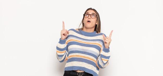 Joven mujer rubia mirando conmocionado, asombrado y con la boca abierta, apuntando hacia arriba con ambas manos para copiar el espacio