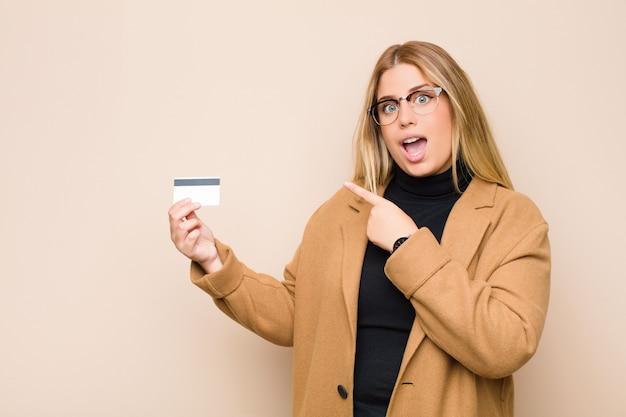 Joven mujer rubia mirando emocionado y sorprendido apuntando hacia un lado y hacia arriba para copiar espacio con una tarjeta de crédito