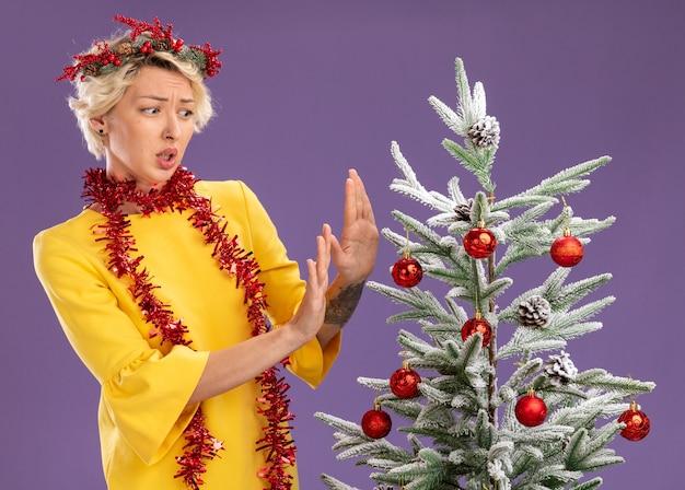 Joven mujer rubia molesta con corona de navidad y guirnalda de oropel alrededor del cuello de pie cerca del árbol de navidad decorado mirándolo haciendo gesto de rechazo aislado en la pared púrpura