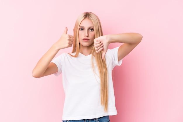 Joven mujer rubia en la pared de color rosa que muestra los pulgares hacia arriba y hacia abajo, difícil elegir el concepto