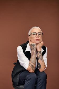 Joven mujer rubia con el pelo corto y brazos cónicos con tatuajes sentado en una silla mientras mantiene las manos debajo de la barbilla de forma aislada