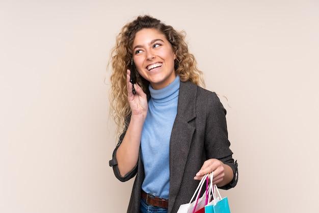 Joven mujer rubia con pelo rizado aislado en pared beige sosteniendo bolsas de la compra y llamando a un amigo con su teléfono celular