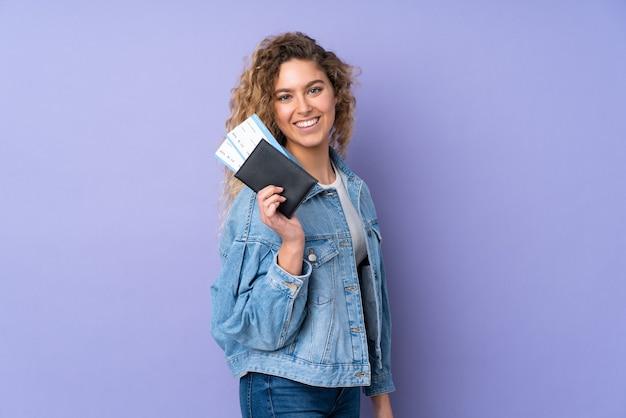 Joven mujer rubia con pelo rizado aislado en la pared púrpura feliz en vacaciones con pasaporte y boletos de avión