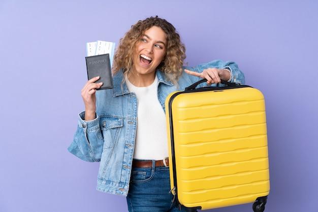 Joven mujer rubia con pelo rizado aislado en pared púrpura en vacaciones con maleta y pasaporte y sorprendido