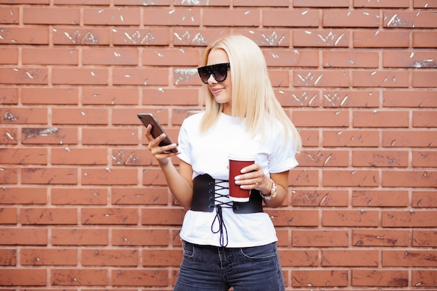 Joven mujer rubia de pie en la calle tomando café para ir y usando teléfono móvil