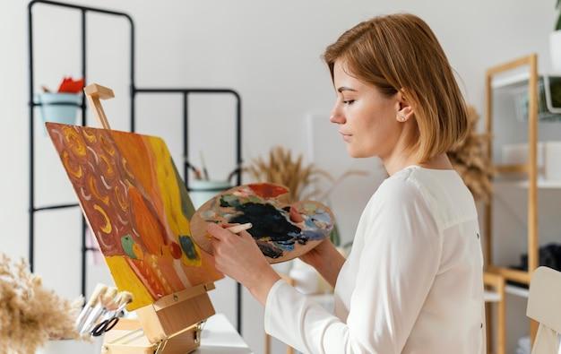 Joven mujer rubia pintando con acrílicos