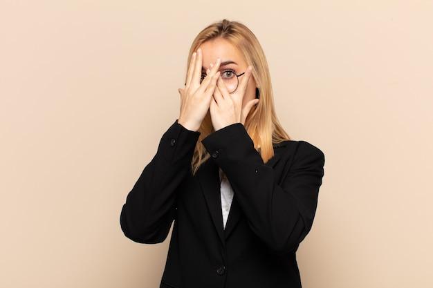Joven mujer rubia que cubre la cara con las manos, mirando entre los dedos con expresión de sorpresa y mirando hacia un lado