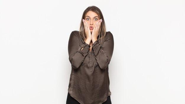 Joven mujer rubia que se siente conmocionada y asustada, mirando aterrorizada con la boca abierta y las manos en las mejillas