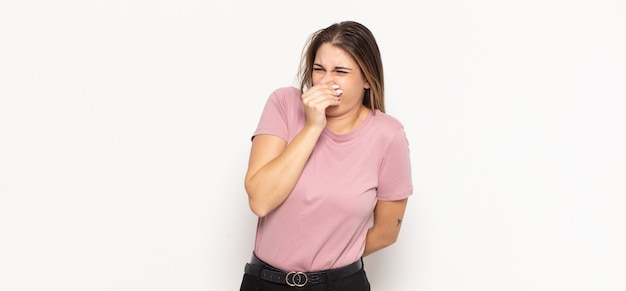 Joven mujer rubia que se siente disgustada, tapándose la nariz para evitar oler un hedor desagradable y desagradable