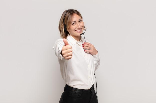 Joven mujer rubia que se siente orgullosa, despreocupada, segura y feliz, sonriendo positivamente con los pulgares hacia arriba