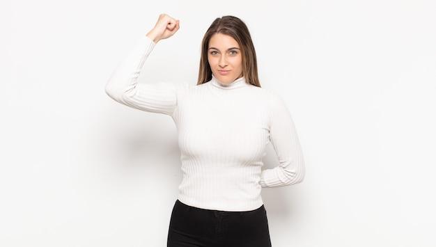 Joven mujer rubia que se siente seria, fuerte y rebelde, levanta el puño, protesta o lucha por la revolución