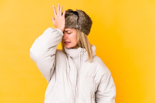Joven mujer rubia con ropa de invierno aislada joven mujer rubia aislada sobre fondo amarillo