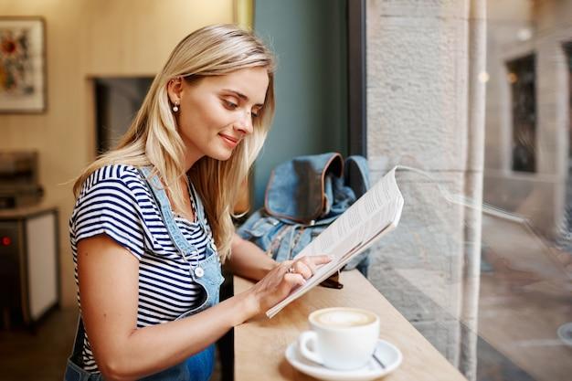 Joven mujer rubia sentada en la cafetería y leyendo