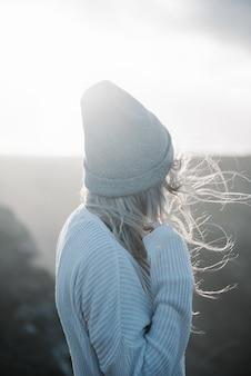 Joven mujer rubia con sombrero caminando por la playa en un clima ventoso