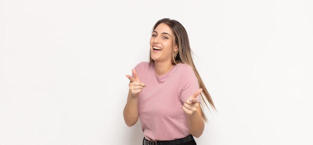Joven mujer rubia sonriendo con una actitud positiva, exitosa y feliz apuntando a la cámara, haciendo un signo de pistola con las manos