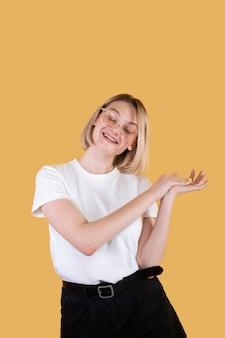 Joven mujer rubia sonriendo aislado en amarillo