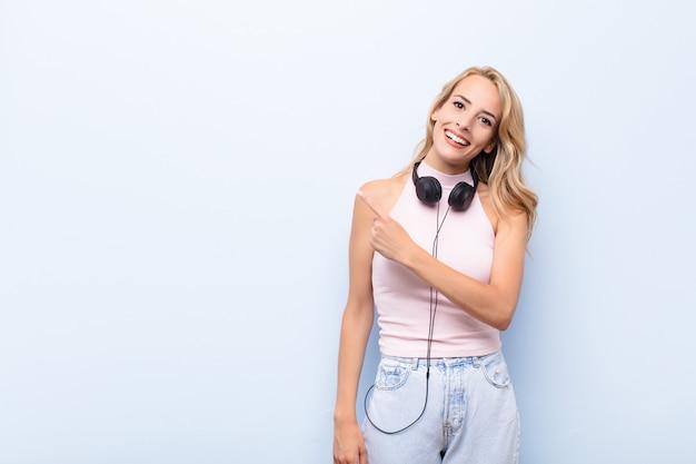 Joven mujer rubia sonriendo alegremente, sintiéndose feliz y apuntando hacia un lado y hacia arriba, mostrando el objeto en el espacio de la copia escuchando música