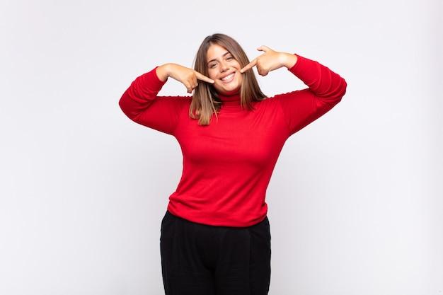 Joven mujer rubia sonriendo con confianza apuntando a su propia sonrisa amplia, actitud positiva, relajada y satisfecha