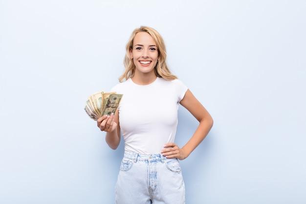 Joven mujer rubia sonriendo felizmente con una mano en la cadera y actitud segura, positiva, orgullosa y amigable con billetes de dólar