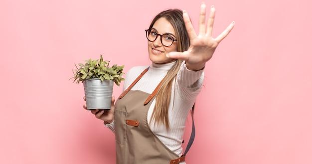 Joven mujer rubia sonriendo y mirando amistosamente, mostrando el número cinco o quinto con la mano hacia adelante, contando hacia atrás