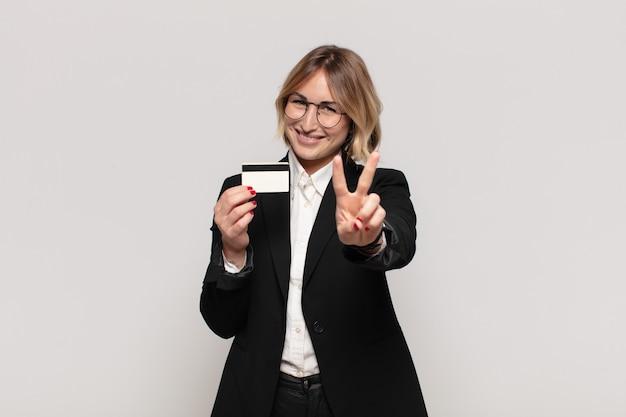 Joven mujer rubia sonriendo y mirando amistosamente, mostrando el número dos o el segundo con la mano hacia adelante, contando hacia atrás