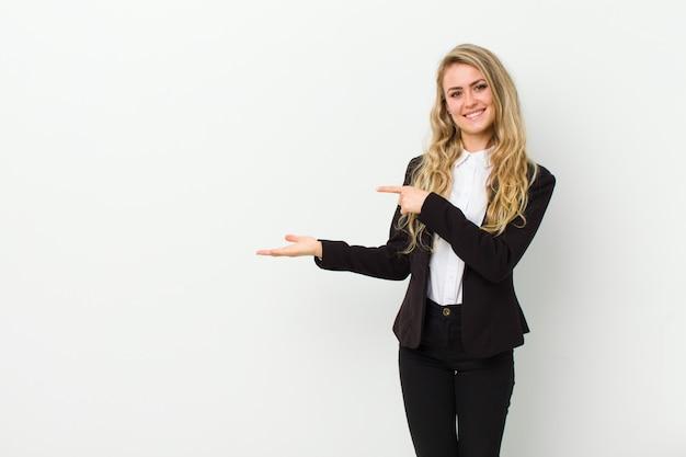 Joven mujer rubia sonriendo, sintiéndose feliz, despreocupada y satisfecha, apuntando al concepto o idea en el espacio de la copia en el lado contra la pared blanca