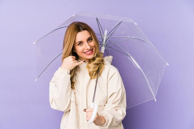 Joven mujer rubia sosteniendo un paraguas y mostrando un gesto de llamada de teléfono móvil con los dedos.