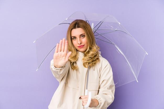 Joven mujer rubia sosteniendo un paraguas de pie con la mano extendida que muestra la señal de stop