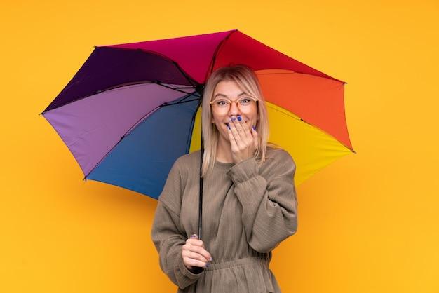 Joven mujer rubia sosteniendo un paraguas sobre la pared amarilla aislada con expresión facial sorpresa