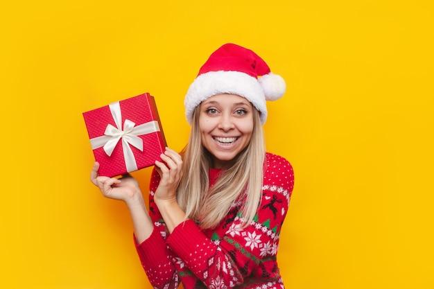 Una joven mujer rubia con un suéter cálido de ciervo rojo y un gorro de papá noel muestra una caja de regalo de navidad