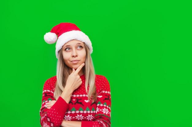 Una joven mujer rubia con un suéter de ciervo rojo y un sombrero de santa claus piensa mirar hacia otro lado en el espacio de la copia