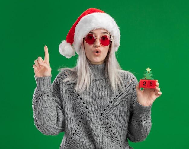 Joven mujer rubia en suéter de invierno y gorro de papá noel con gafas rojas sosteniendo cubos de juguete con fecha de navidad mirando sorprendido mostrando el dedo índice de pie sobre fondo verde