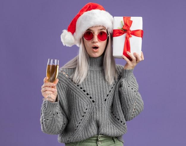 Joven mujer rubia en suéter de invierno y gorro de papá noel sosteniendo un regalo y una copa de champán mirando a la cámara sorprendido de pie sobre fondo púrpura