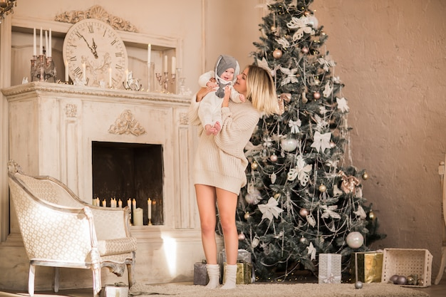 Joven mujer rubia en suéter largo beige abrazando a little baby boy en traje de navidad