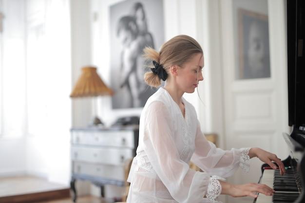 Joven mujer rubia tocando el piano durante el día