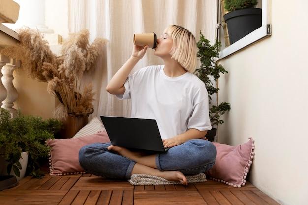 Joven mujer rubia trabajando desde casa en el piso