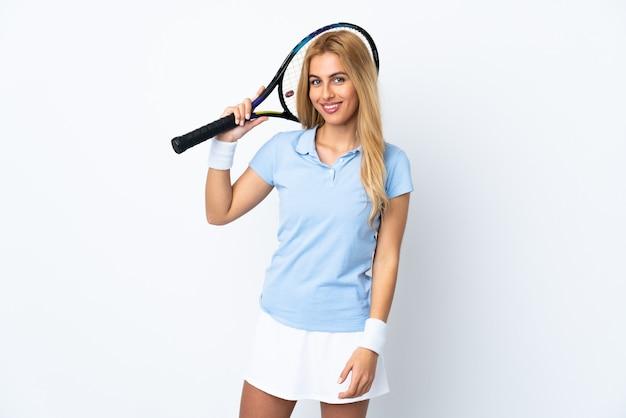 Joven mujer rubia uruguaya sobre pared blanca aislada jugando al tenis