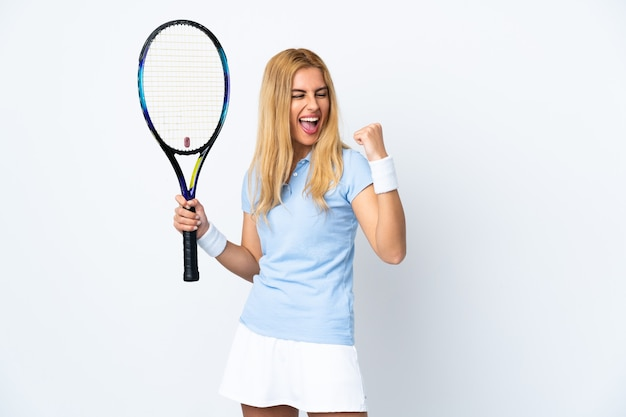 Joven mujer rubia uruguaya sobre pared blanca aislada jugando tenis y celebrando una victoria