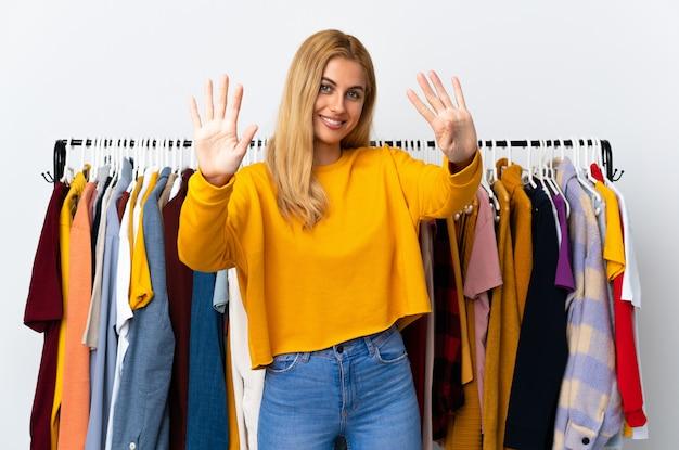 Joven mujer rubia uruguaya en una tienda de ropa contando nueve con los dedos