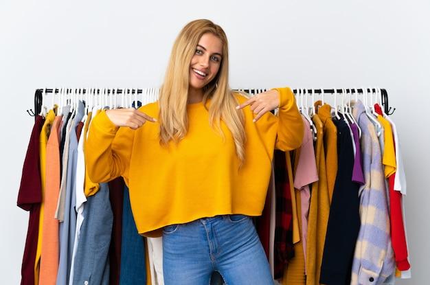 Joven mujer rubia uruguaya en una tienda de ropa orgullosa y satisfecha
