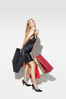 Joven mujer rubia vestida de negro de compras en blanco