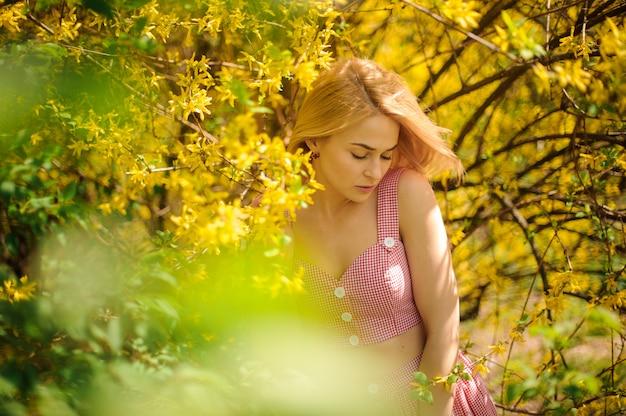 Joven mujer rubia vestida con un vestido rosa de pie cerca del árbol floreciente amarillo