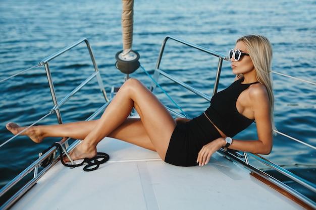 Joven mujer rubia en vestido negro corto posando en un barco de yates