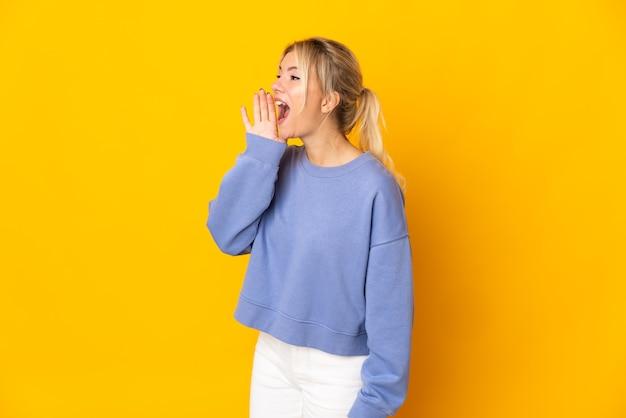 Joven mujer rusa aislada en la pared amarilla gritando con la boca abierta hacia un lado
