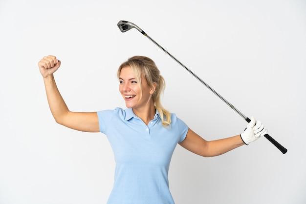 Joven mujer rusa aislada sobre fondo blanco jugando al golf y celebrando una victoria
